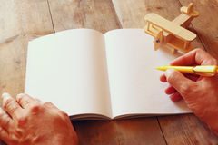 Open blank notebook and woman hands next to toy aeroplane on wooden table. retro style  filtered image Stock Images