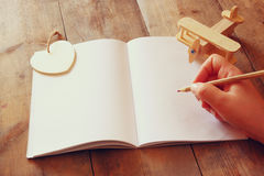 Open blank notebook and woman hands next to toy aeroplane on wooden table. retro style  filtered image Stock Photos