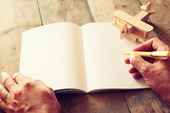 Open blank notebook and woman hands next to toy aeroplane on wooden table. retro style  filtered image Stock Image