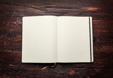 Open blank notepad with empty white pages. Laying on a old dark wooden table Stock Photos