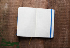 Open blank notepad with empty white pages. Laying on a wooden table Royalty Free Stock Photos