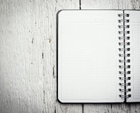 Open blank notepad with empty white pages. Laying on a wooden table Royalty Free Stock Photo