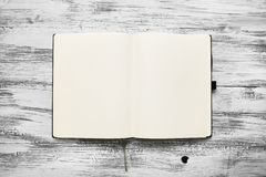 Open blank notepad with empty white pages. Laying on a wooden table Royalty Free Stock Image