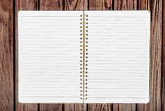Open blank notepad with empty white pages laying. On a wooden table Royalty Free Stock Photos