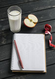 Open a blank Notepad, a glass of natural yoghurt and an apple. The concept of healthy and dieting. Stock Photos