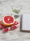Open a blank Notepad, a grapefruit, a glass of water and measuring tape on a light wooden table. Stock Images