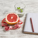 Open a blank Notepad, a grapefruit, a glass of water and measuring tape on a light wooden table. Royalty Free Stock Photography