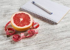 Open a blank Notepad, grapefruit and measuring tape on a light wooden table. Stock Image