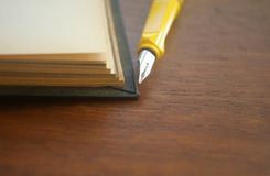 Open blank old notebook on table with yellow pen Stock Images