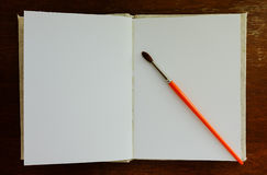 Open blank old notebook on wooden table with one round brush Royalty Free Stock Photo