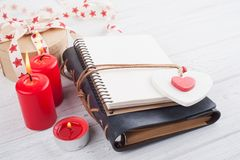 Open blank planner, with lit candles and red heart. Lily flowers on white wooden table Stock Images