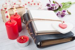 Open blank planner, with lit candles and red heart. Lily flowers on white wooden table Royalty Free Stock Photography