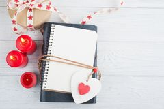 Open blank planner, with lit candles and red heart. Lily flowers on white wooden table Royalty Free Stock Photos