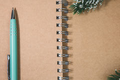 Open blank spiral notepad with metal pen christmas concept Fir t. Open blank spiral notepad with metal pen, christmas concept Fir tree branch Royalty Free Stock Image