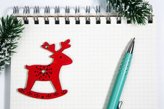 Open blank spiral notepad with red wooden deer christmas concept. Open horizontal blank spiral notepad with red wooden deer, christmas concept Fir tree branch Royalty Free Stock Images