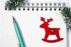 Open blank spiral notepad with red wooden deer christmas concept. Open horizontal blank spiral notepad with red wooden deer, christmas concept Fir tree branch Stock Photo
