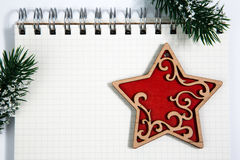 Open blank spiral notepad with red wooden star christmas concept. Open horizontal blank spiral notepad with red wooden toy star, christmas concept Fir tree Royalty Free Stock Photos
