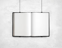 Open blank textbook on white concrete wall Stock Photography
