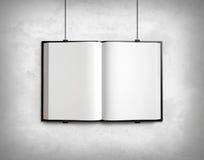 Open blank textbook on white concrete wall Stock Photo