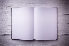 Open blank textbook on white wooden weathered background. Royalty Free Stock Photos