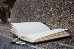 Open a blank white notebook, pen Stock Images