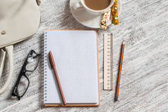 Open a blank white notebook, pen, women's bag, ruler, pencil and cup of coffee Stock Photo
