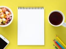 Open blocnote op de spiraal met een schone witte pagina, een Kop met thee, karamels in een kom, een smartphone en een kleurenpotl stock fotografie