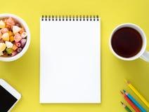Open blocnote op spiraal met schone witte pagina, kop met thee, karamels in een kom, smartphone en kleurenpotlood stock afbeeldingen