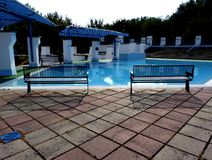 Open blue kids` swimming pool with benches and awnings. Colorful concrete paving and concrete stairs royalty free stock photography