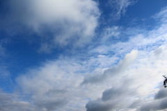 Open blue sky with small dark clouds Royalty Free Stock Photos