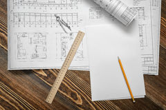 Open blueprints on wooden table background with a pencil, a ruler and compasses lying beside. Stock Images