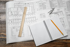 Open blueprints on wooden table background with a pencil, a ruler and compasses lying beside. Royalty Free Stock Image