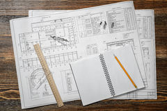 Open blueprints on wooden table background with a pencil, a ruler and compasses lying beside. Royalty Free Stock Photo