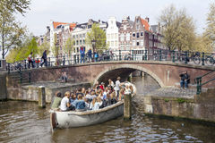 Open boat full of young people under bridge in amsterdam canal o Royalty Free Stock Photo