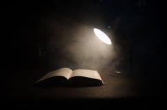 Open boek dichtbij gloeiende schemerlamp op donkere achtergrond, Lamp en geopend boek met rook op achtergrond surreal Royalty-vrije Stock Foto