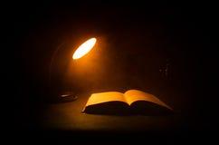 Open boek dichtbij gloeiende schemerlamp op donkere achtergrond, Lamp en geopend boek met rook op achtergrond surreal Stock Fotografie