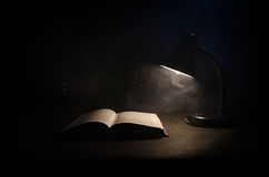 Open boek dichtbij gloeiende schemerlamp op donkere achtergrond, Lamp en geopend boek met rook op achtergrond surreal Stock Foto's