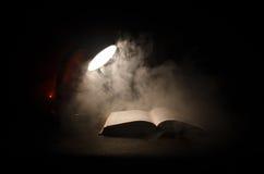 Open boek dichtbij gloeiende schemerlamp op donkere achtergrond, Lamp en geopend boek met rook op achtergrond surreal Royalty-vrije Stock Afbeeldingen
