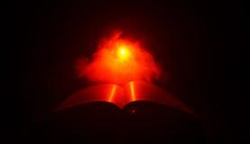 Open boek dichtbij gloeiende schemerlamp op donkere achtergrond, Lamp en geopend boek met rook op achtergrond surreal Royalty-vrije Stock Fotografie