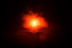 Open boek dichtbij gloeiende schemerlamp op donkere achtergrond, Lamp en geopend boek met rook op achtergrond surreal Royalty-vrije Stock Foto's