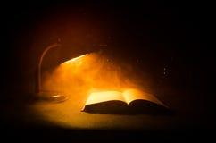 Open boek dichtbij gloeiende schemerlamp op donkere achtergrond, Lamp en geopend boek met rook op achtergrond surreal Royalty-vrije Stock Afbeelding