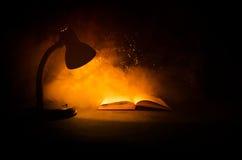 Open boek dichtbij gloeiende schemerlamp op donkere achtergrond, Lamp en geopend boek met rook op achtergrond surreal Stock Afbeeldingen