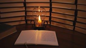 Open boek en een brandende kaars stock videobeelden