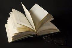 Open boek en glazen op zwarte achtergrond Stock Fotografie