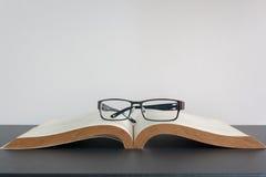 Open boek en oogglazen op bureau Royalty-vrije Stock Afbeeldingen