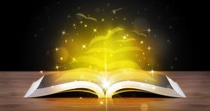 Open boek met gouden gloed vliegende document pagina's royalty-vrije stock foto