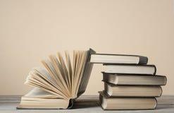 Open boek, boek met harde kaftboeken op houten lijst en kleurrijke muur schaar en potloden op de achtergrond van kraftpapier-docu stock foto's