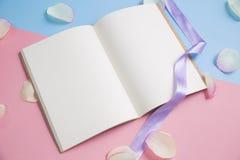 Open boek met roze bloemblaadjes op pastelkleurachtergrond Stock Foto's