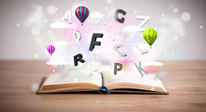 Open boek met vliegende 3d brieven op concrete achtergrond Stock Fotografie