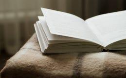 Open boek op een deken, op tegenover het venster Royalty-vrije Stock Foto's